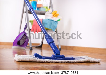 Close up of mop on the parquet and cleaning supplies on the ladder in background - stock photo