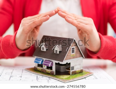 Close-up of mortgage agent hands with family house model in real estate agency. Concept of real estate loan agreement. Shallow depth of field. - stock photo