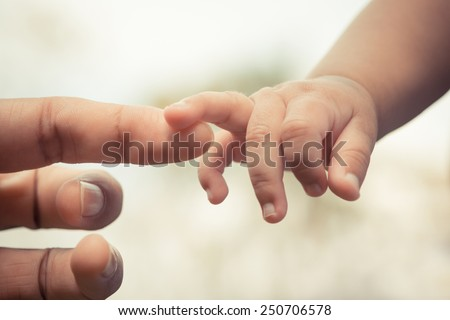 Close-up of mother and baby's hands - stock photo