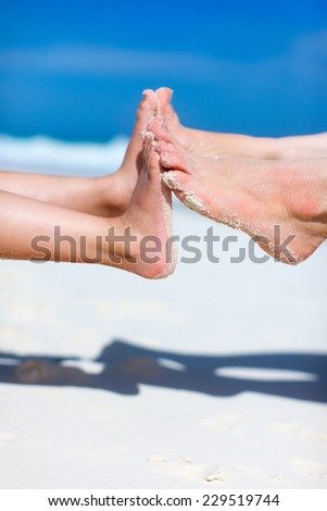 Close up of mother and daughter feet on a tropical sandy beach - stock photo