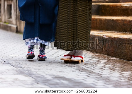 Close up of mother and daughter wearing kimono and geta traditional Japanese footwear. - stock photo