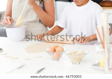 Close up of mother and son preparing a dough together in the kitchen - stock photo
