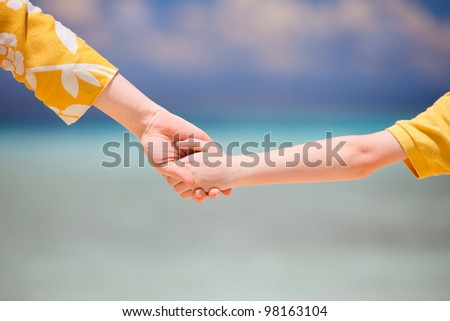 Close up of mother holding her son hand - stock photo