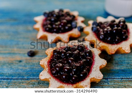 Close-up of mouth-watering tarts made from unleavened dough are on the table, the cook is going to serve them with fresh berries - stock photo