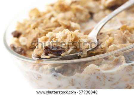 Close-up of muesli in spoon on glass bowl of muesli with milk. - stock photo