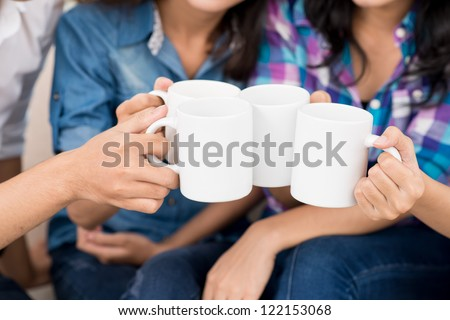 Close-up of mugs in hands of teenagers - stock photo