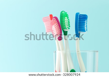 Close up of multicolor toothbrushes in glass - stock photo