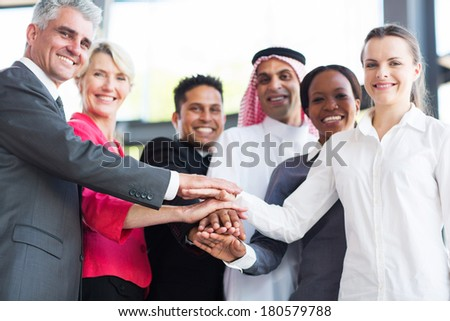 close up of multiracial business team putting their hands together, focus on hands - stock photo