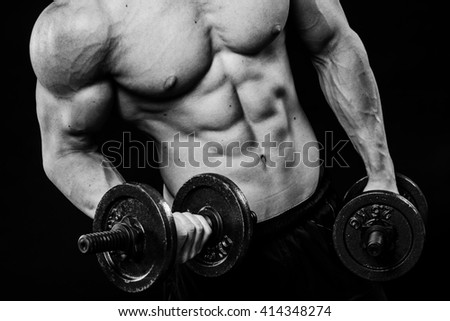 Close up of muscular bodybuilder guy doing exercises with weights dumbbell over isolated black background. Black and white - stock photo