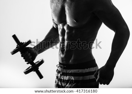 Close up of muscular bodybuilder guy doing exercises with weights dumbbell over light background.. Black and white - stock photo
