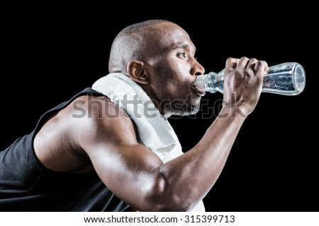 Close-up of muscular man drinking water against black background