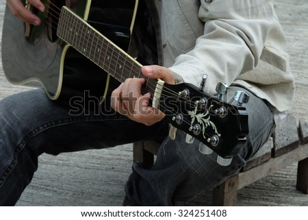 Close-up of musician playing guitar, selective focus - stock photo