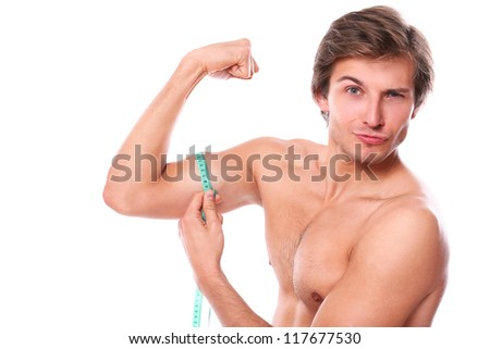 Close up of naked torso man measuring his muscle over a white background - stock photo