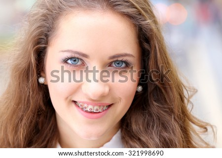 Close Up of natural beauty smiling teen face with braces - stock photo