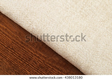 Close up of natural white linen napkin on natural brown wooden rustic textured surfaces background - stock photo
