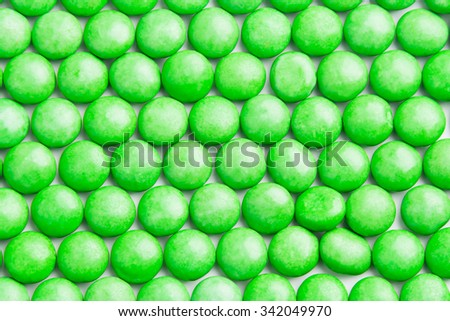 Close up of neatly arranged in rows green milk chocolate candies with crisp shell