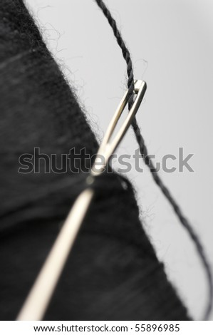 Close-up of needle with black thread in black reel on light background. - stock photo