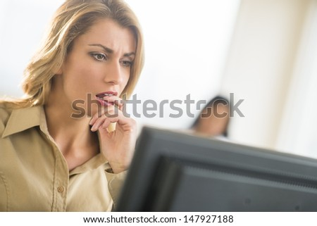 Close-up of nervous young businesswoman looking at computer with colleague in background - stock photo
