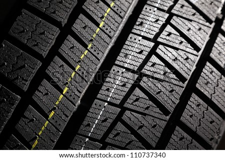 Close-up of new high performance modern winter car tire. - stock photo