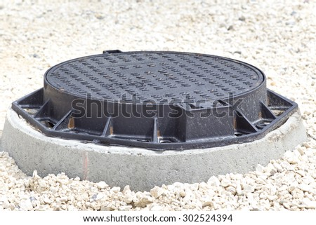Close up of new metal cover over concrete manhole at road construction site - stock photo