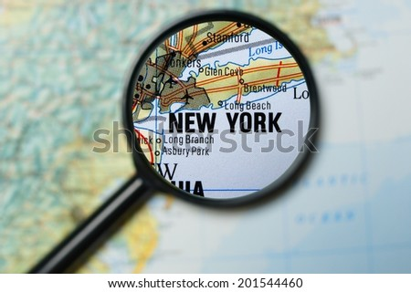 Close up of New York City under a magnifying glass on a map         - stock photo