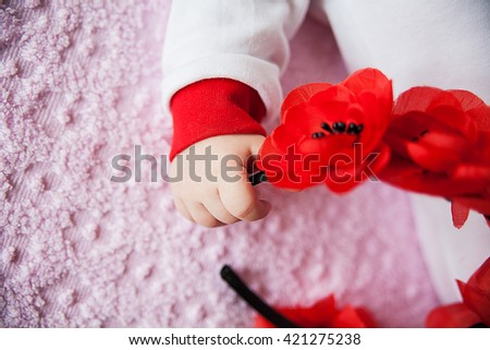 Close-up of newborn baby hand holding a of flowers