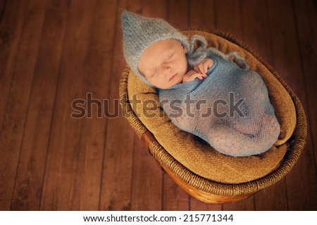 Close up of newborn baby in basket with wrap and hat - stock photo