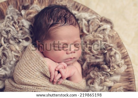 Close up of newborn swaddled with fingers intertwined - stock photo