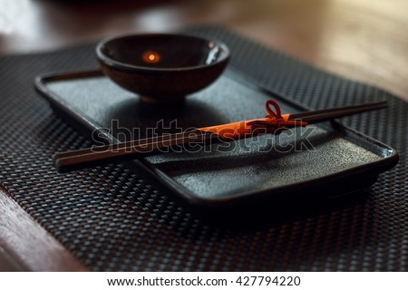 Close up of nice serving plate for sushi, composed of beautiful wooden chopsticks wrapped in orange paper, tray and small bowl.  Ready to eat some tasty SUSHI :P - stock photo