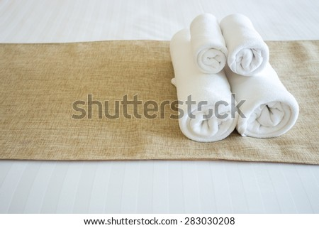 Close up of nice towels on white bed sheet with yellow ribbon - stock photo