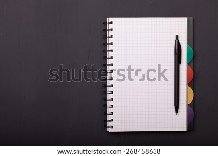 close up of notebook and pen on the black wooden table - stock photo