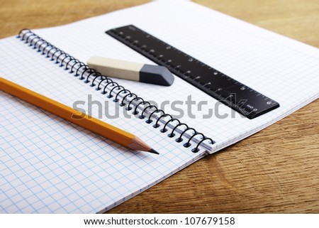 Close up of notebook with pencil and eraser - stock photo