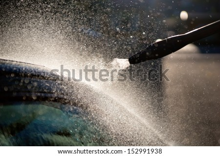Close up of nozzle of high pressure washer used on car - stock photo