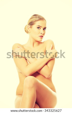 Close up of nude woman sitting on something invisible.
