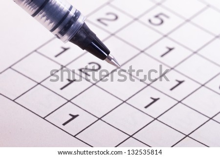 Close up of numbers crossword puzzle with black pen. - stock photo