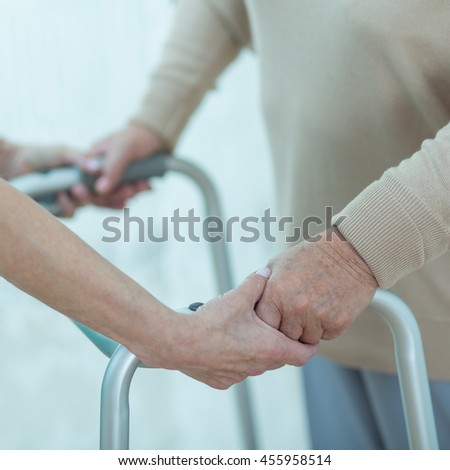 Close-up of nurse helping disabled elderly lady with a walking frame