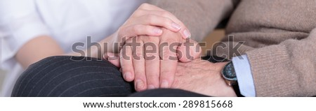 Close-up of nurse holding aged man's hands - stock photo