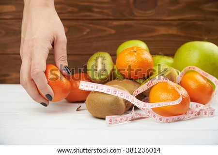 Close up of nutritionist's hand measuring orange with tape over healthy fruit background. Concept of fat prevention and  lose weight.