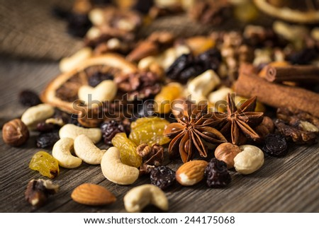 Close-up of nuts and dried fruits mix on wooden surface. Focused on anise star.