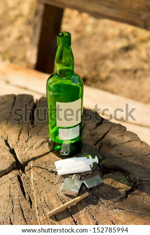 Close-up of objects - symbols of addictive habits: a bottle of alcoholic beverage, a brown cigarette, a syringe and a liighter - stock photo