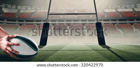 Close-up of of sports player holding ball against rugby pitch - stock photo