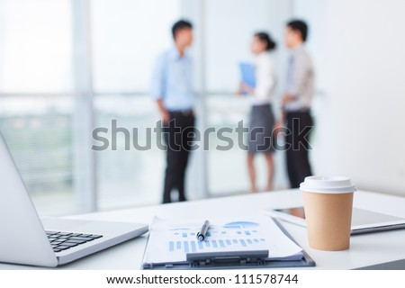 Close-up of office desk with business team behind - stock photo