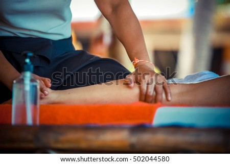 Close up of Oil Massage Spa at leg by Hand in tropical garden for wellness and healthy background