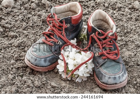 close up of old and dirty little baby booties on clay - heart shaped shoelace with blossoming cherry - stock photo