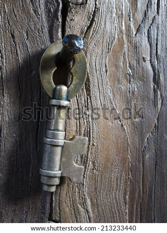 Close-up of Old Brass Key Hanging from a Brass Nail attached to a grainy wooden beam - stock photo