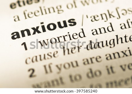 Close up of old English dictionary page with word anxious - stock photo
