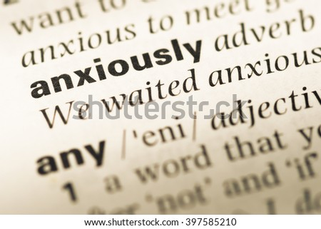 Close up of old English dictionary page with word anxiously - stock photo