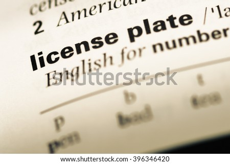 Close up of old English dictionary page with word license plate - stock photo
