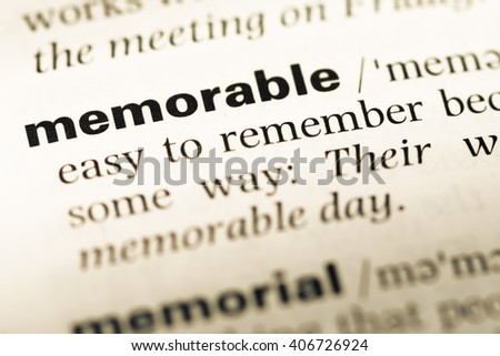 Close up of old English dictionary page with word memorable - stock photo