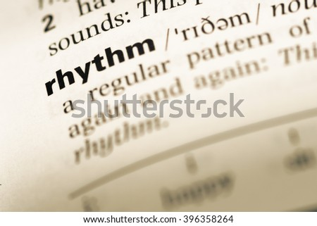 Close up of old English dictionary page with word rhythm